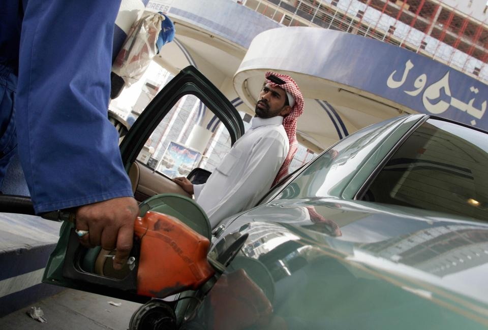 A worker at a gas station fills a Saudi